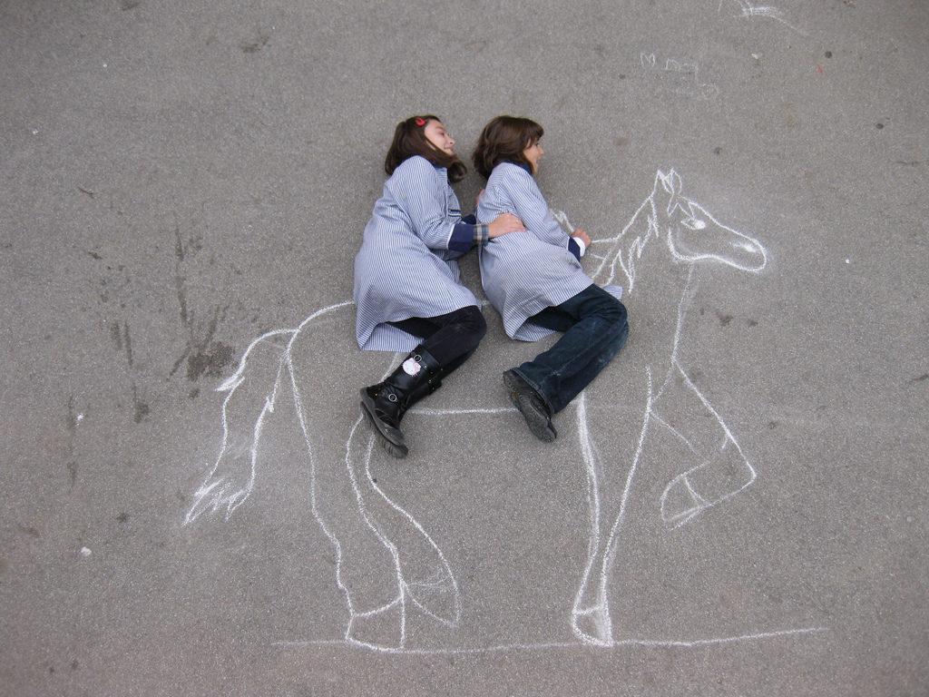Alumnos de quinto creando dibujo con tiza en el patio para aplicar conceptos de la perspectiva.