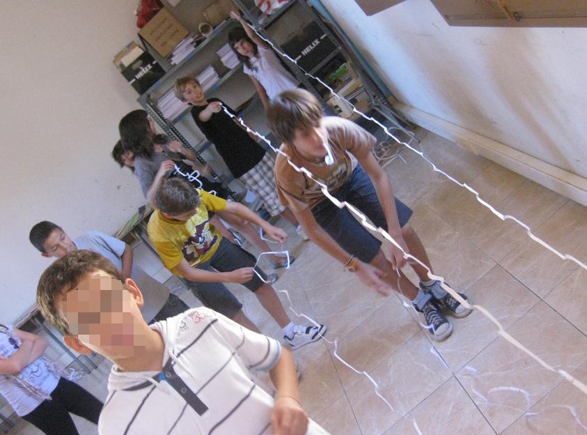 Alumnos comprobando quién ha conseguido transformar un hoja de papel en la tira de papel más larga.